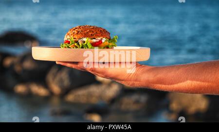 Donna di mano che trattiene la piastra di legno con fishburger davanti al mare Foto Stock