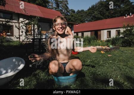 Felice fratello e sorella gioca con acqua in giardino Foto Stock