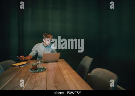 Uomo seduto in ufficio, lavora fino a tardi nella sua azienda start-up, ascoltando musica Foto Stock