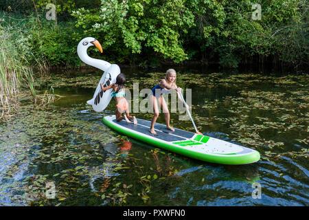 Due ragazze in uno stagno con piscina gonfiabile giocattolo in forma di cigno e SUP board Foto Stock