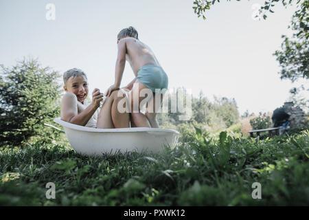 Fratello e Sorella gioca con acqua nella piccola vasca da bagno in giardino Foto Stock