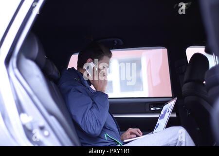 Business man utilizza un computer portatile e il telefono cellulare è seduto in macchina Foto Stock