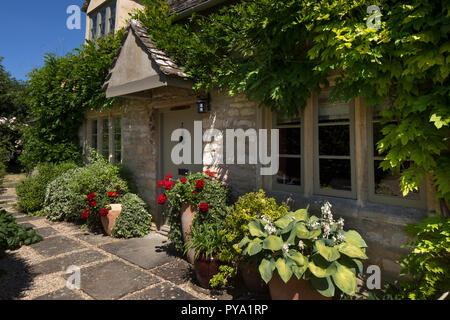 Sportello anteriore del cottage nel Giardino inglese con il glicine e vasi di rose e hosta,l'Inghilterra,l'Europa Foto Stock