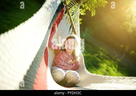 Felice bambina rilassante in amaca sulla bella giornata d'estate. Carino bambino divertirsi nella primavera del giardino. Vacanza in famiglia in estate. Foto Stock