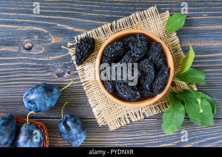 Le prugne secche in un vaso di argilla e prugne fresche, foglie su un tavolo di legno. Prugne fresche per una vita sana.