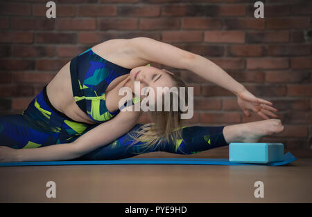 Giovane donna graziosa in sport vestiti sulla formazione esegue esercizi Foto Stock