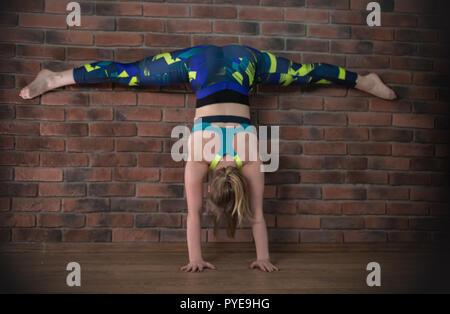 Giovane donna graziosa in sport vestiti sulla formazione esegue split in piedi sulle mani Foto Stock