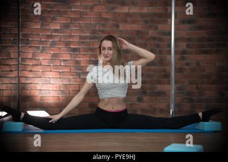 Giovane donna graziosa in sport vestiti sulla formazione esegue split Foto Stock