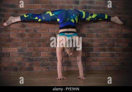 Giovane donna graziosa in sport vestiti sulla formazione esegue split in piedi sulle mani da parete Foto Stock