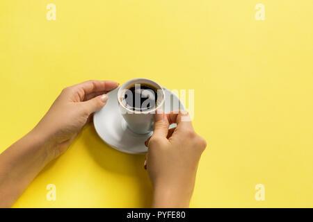 Elevato angolo di donna mani tazza da caffè su sfondo giallo stile minimalista. Appartamento laico, vista dall'alto isolato. Foto Stock