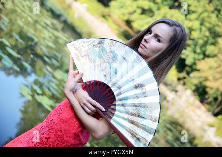 Modello femminile dalla Polonia indossando il tradizionale abito cinese in colore rosso, mantenendo la ventola. Donna che pongono in stile asiatico park. Foto Stock
