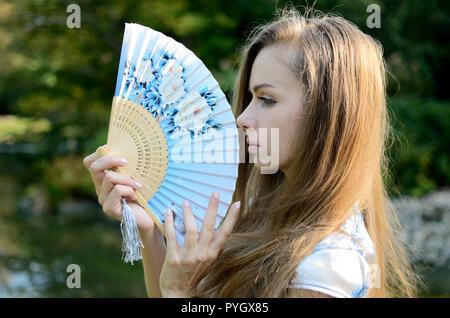 Modello femminile dalla Polonia indossando il tradizionale abito cinese, mantenendo la ventola. Donna che pongono in stile asiatico park. Foto Stock