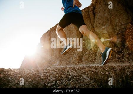 Uno stile di vita sano uomo di mezza età runner in esecuzione sul sentiero di montagna in sunset Foto Stock