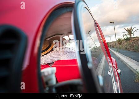 Amore kiss catturata da un vetro auto. Due senior l uomo e la donna baciare con amore e celebrare una vita insieme per sempre. viaggi e vacanze. persone enj Foto Stock