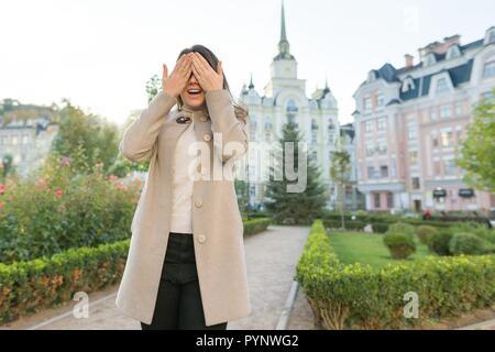 Outdoor ritratto di una giovane donna che copre la sua gli occhi. Foto Stock