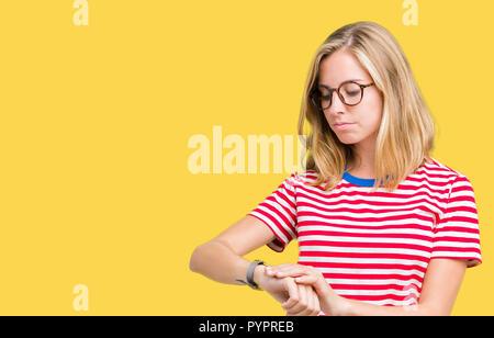 Giovane e bella donna che indossa gli occhiali su sfondo isolato controllando il tempo su orologio da polso, rilassato e fiducioso Foto Stock