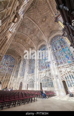 File di sedie di fronte a nord e a ovest le finestre di vetro macchiate sotto la ventola soffitto, Cappella del King's College, Università di Cambridge. Foto Stock