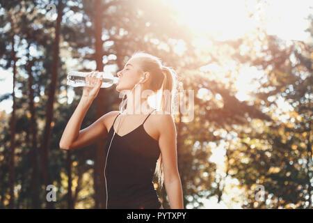 Ritratto di giovane atletico dai capelli lunghi donna che indossa abiti sportish ascoltando musica e acqua potabile nel soleggiato parco, uno stile di vita sano e concetto di persone