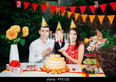 Festa di compleanno per bambini tema. famiglia di tre persone caucasica seduto nel cortile della casa in una festosa tavola decorata in buffi cappelli e berretti su thei Foto Stock