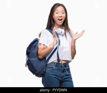 Giovane donna asiatica che indossa uno zaino e cuffie su sfondo isolato molto felici ed eccitati, vincitore espressione celebrando la vittoria urlando wit