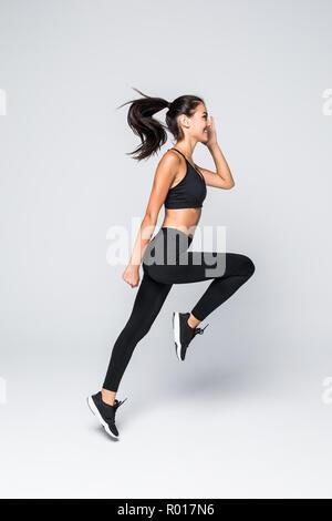 Lunghezza completa immagine del jumping donna fitness su sfondo grigio Foto Stock