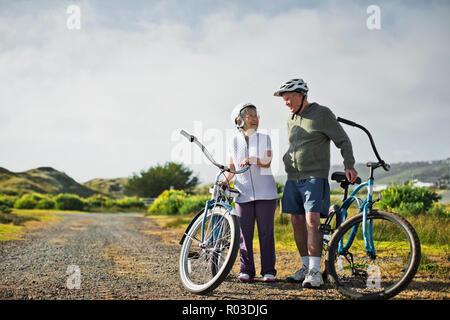 Felice coppia di anziani chat assieme come si prendono una pausa dai percorsi in bicicletta lungo una strada di campagna. Foto Stock