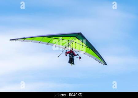 Uomo in deltaplano in autunno con cielo blu, cercando un posto per atterrare sulla South Downs in East Sussex, Inghilterra, Regno Unito.