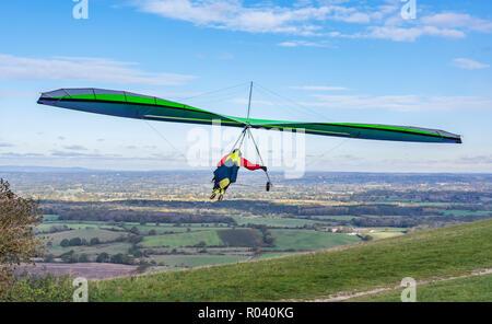 L'uomo battenti un deltaplano in autunno dopo il decollo dalla Devil's Dyke sulla South Downs in East Sussex, Inghilterra, Regno Unito. POV.