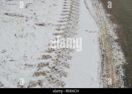 Abstract sfondo invernale sulla neve, close-up della pista dalla vettura del battistrada dei pneumatici Foto Stock