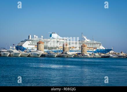 La foto in orizzontale del grande oceano mare cruiser. Barca è in vecchio antico porto di Rodi città capitale. Parecchie navi di piccole dimensioni sono in parte anteriore del vecchio mulino in pietra Foto Stock