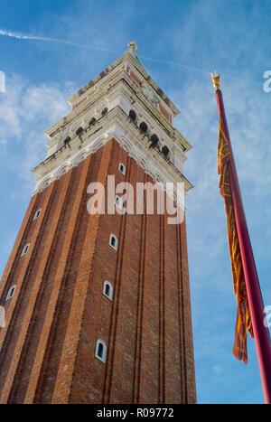 Il Campanile - Il Campanile di San Marco e un Rosso e Oro bandiera veneziana in Piazza San Marco a Venezia, Italia Foto Stock