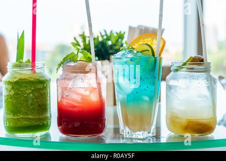 Varietà di iced cocktail alla frutta e mocktail sul tavolo di vetro Foto Stock