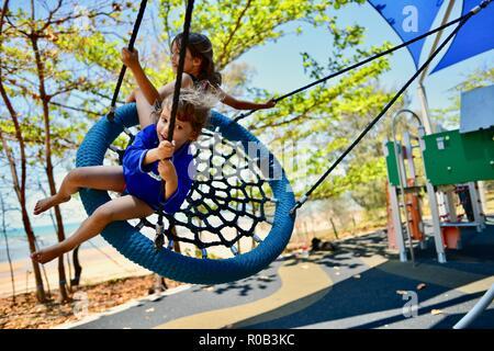 Due bambini che giocano su un nido swing, Balgal beach, QLD, Australia Foto Stock