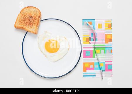 Uovo fritto in una a forma di cuore su una piastra con toast vista superiore con ombra su sfondo bianco