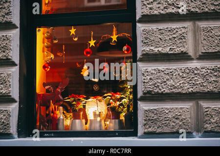 Eleganti decorazioni di natale renne, giocattoli, alberi di Natale, pigne, luci nella finestra in città europea street. Festive arredamento e illuminazione in