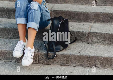 Gambe e borsa closup giovane ragazza carina con valigetta seduti sulle scale Foto Stock
