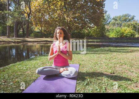 La donna la meditazione e la pratica dello Yoga in Lotus preghiera pongono, Padmasana. La meditazione sulla bella e soleggiata giornata autunnale nel Parco.