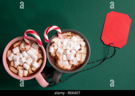 Carta rossa tag legato con una stringa di verde di due tazze con cioccolata calda e mini marshmallows e candy canes, su un tavolo verde Foto Stock