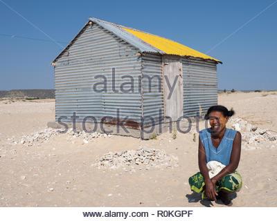 Sarondrano, Madagascar, Aug.08, 2018 - donna accovacciata nella parte anteriore del rifugio di stagno nel villaggio Sarondrano, Madagascar Foto Stock