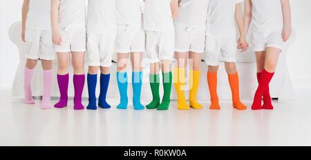 I bambini che indossano colorati calzini arcobaleno. Calzature per bambini raccolta. Varietà di maglia alta del ginocchio calze e collant. Bambino Abbigliamento e capi di vestiario. Kid fash Foto Stock