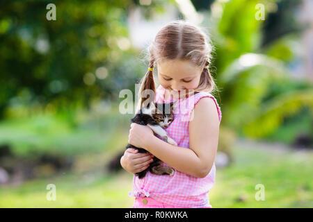 Bambino azienda baby cat. Bambini e animali domestici. Bambina avvolgente poco carino gattino nel giardino estivo. Animale domestico in famiglia con i bambini. I bambini con hom Foto Stock