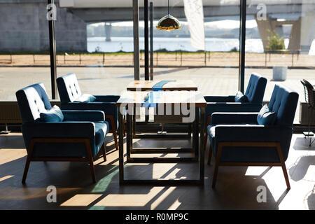 Due piccoli tavoli e quattro sedie intorno e lampada appesa sopra con grande finestra come sfondo Foto Stock