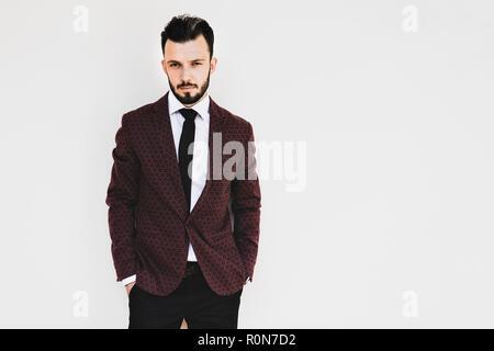 Bello ed elegante uomo alla moda o imprenditore che posano su sfondo bianco  Foto Stock 87857f43a106