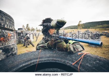 Giovane uomo paintballing, pistola di puntamento Foto Stock