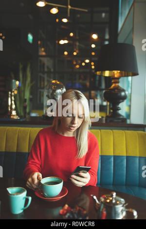 Donna che utilizza il cellulare mentre un caffè