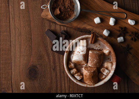 Scatto dall'alto di una grande tazza di cioccolata calda con marshmallows su un legno rustico tavolo da cucina, con copia spazio. Foto Stock