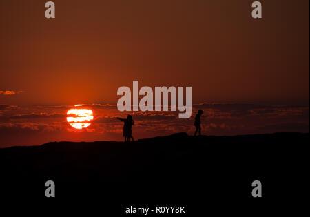 Silhouette ispiratore di un giovane ragazzo vincendo la ragazza puntando verso un tramonto mentre il suo rivale tristemente foglie. Foto Stock