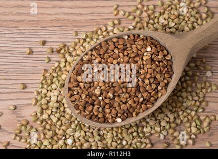 Fresco e naturale del grano saraceno in cucchiaio di legno. Su un tavolo di legno. Vista dall'alto. Foto Stock