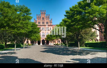 La facciata anteriore della capmus principale di Yuriy Fedkovych Chernivtsi Università Nazionale contro lo sfondo del giardino con alberi verdi e hedge. Foto Stock