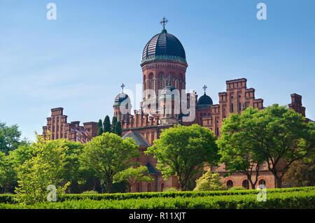 La facciata della capmus principale di Yuriy Fedkovych Chernivtsi Università Nazionale contro lo sfondo del giardino con alberi verdi e un elevato lante Foto Stock